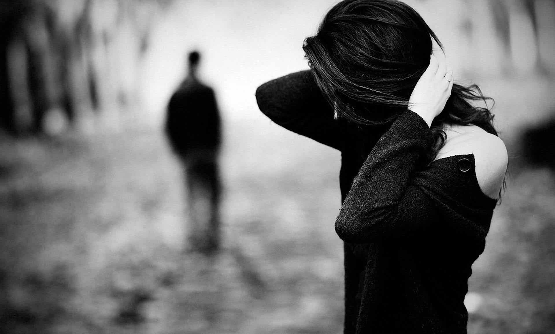 A black and white photo of a man walking away from a woman.