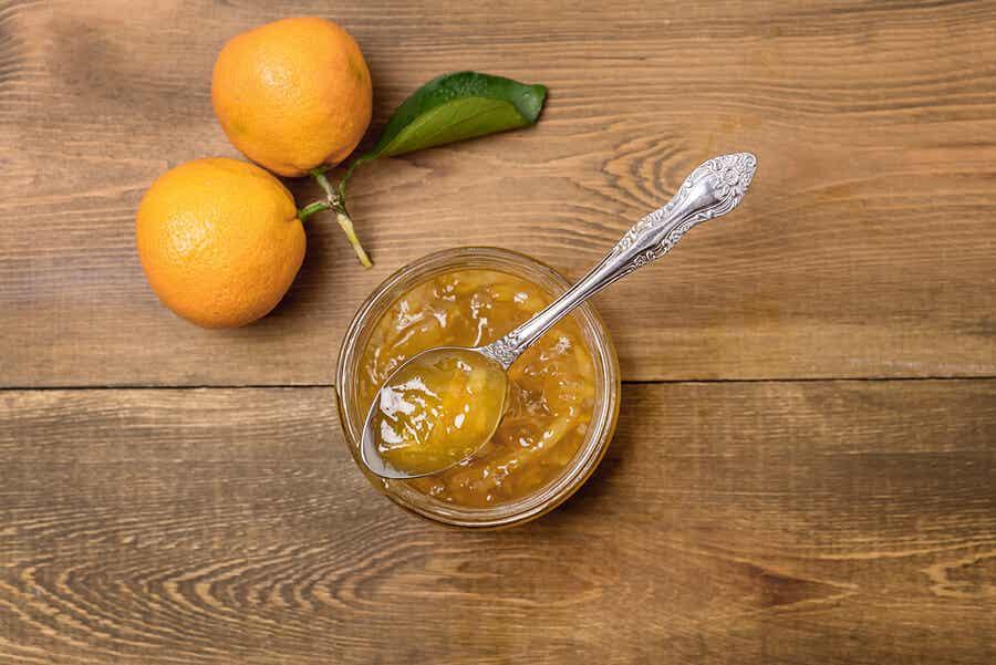 Δύο πορτοκάλια και ένα μπολ με μαρμελάδα πορτοκάλι.