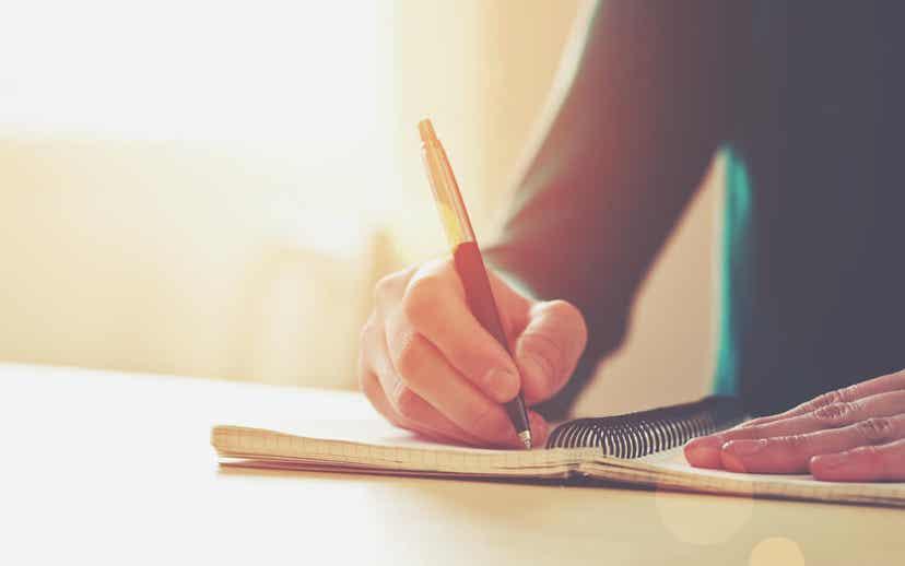En kvinne som skriver i notatblokken.