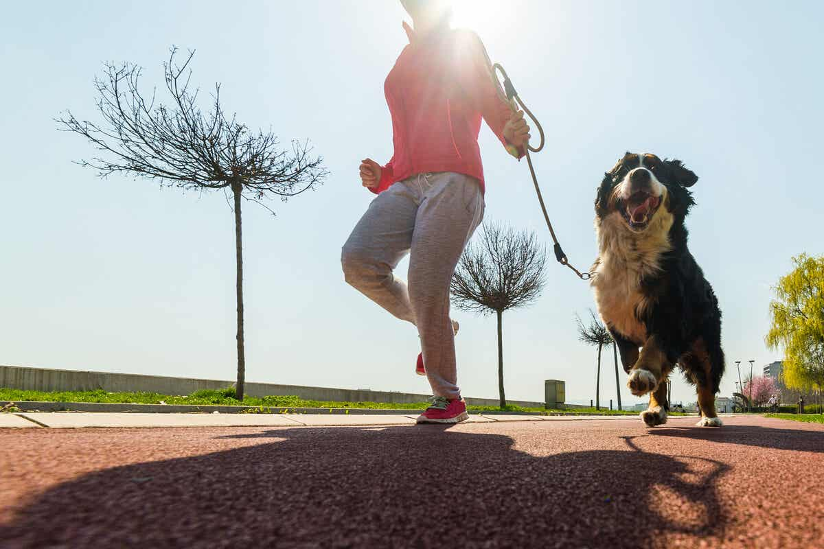 A woman running with her dog.