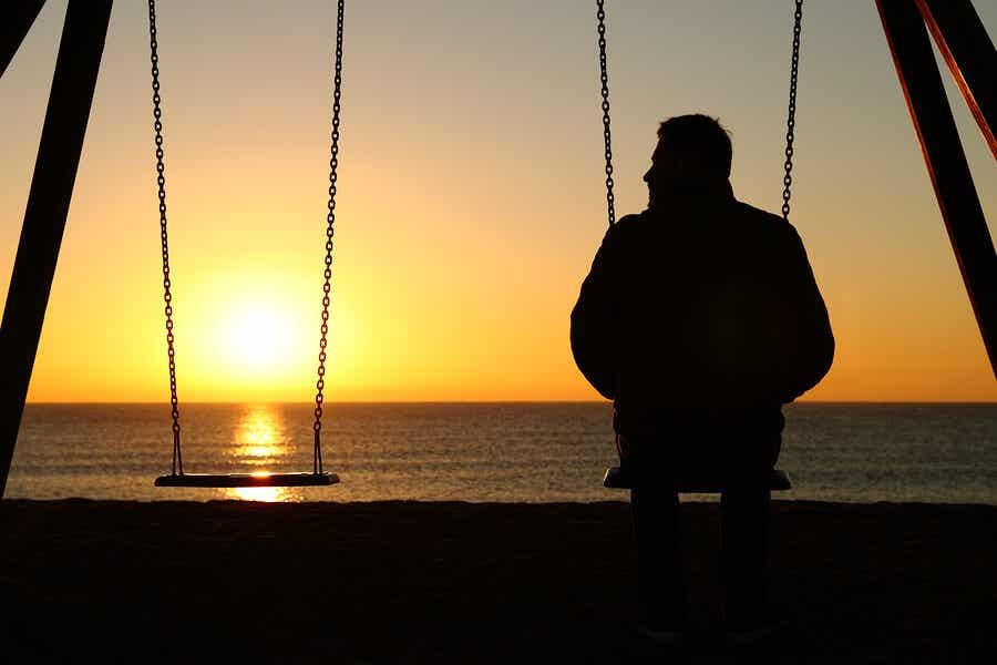 En mann som sitter på en huske og ser på solnedgangen over havet.