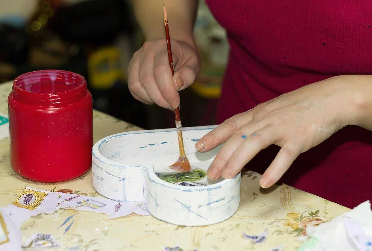 A woman using a paint brush to cover a heart-shaped box with mod podge.
