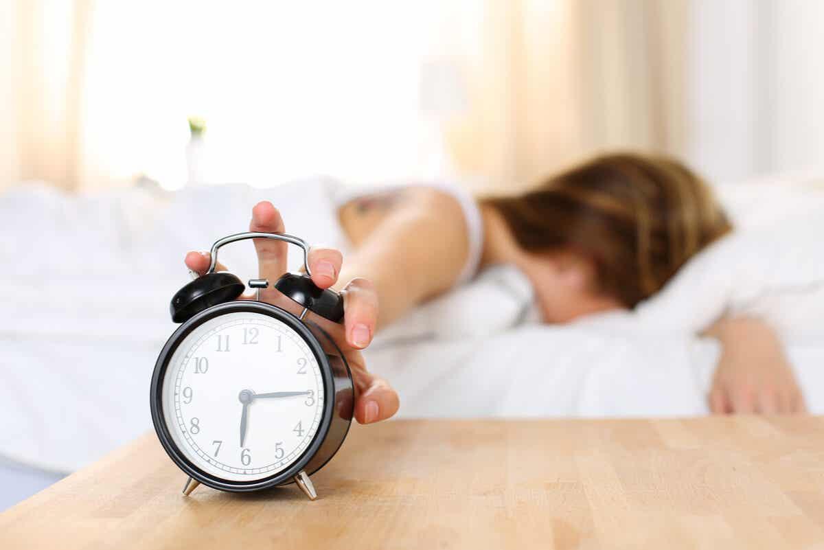 Eine Frau, die ihren Wecker auf Snooze stellt.