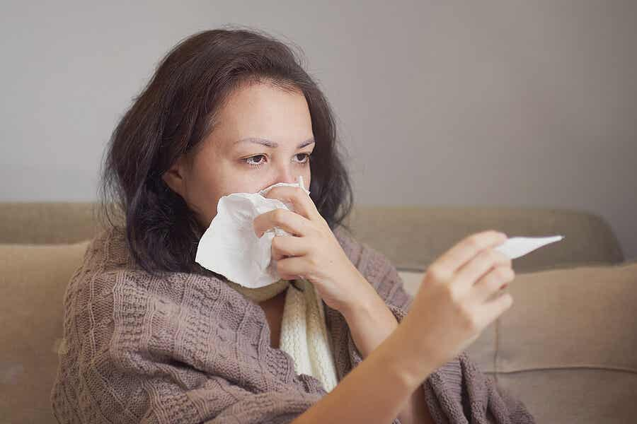 A woman with a runny nose taking her temperature.