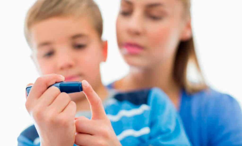 Bør barn spise sjokolade? En mor hjelper barnet sitt med å kontrollere insulinnivået.