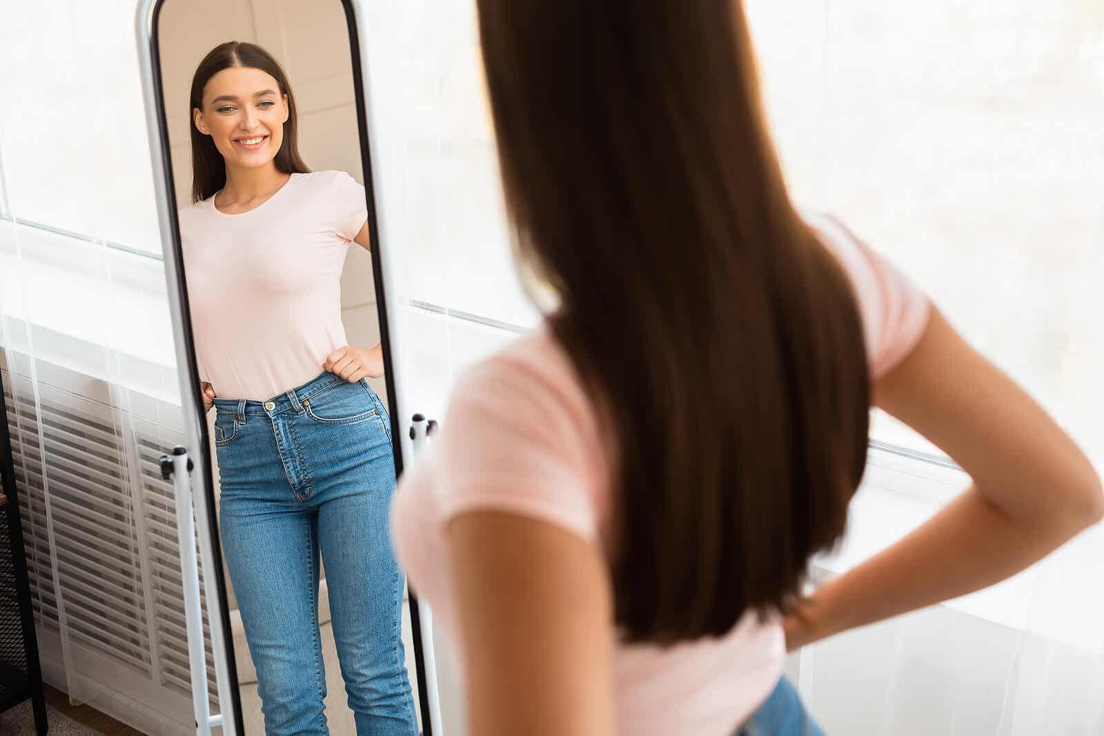 Dziewczyna uśmiecha się, patrząc na siebie w lustrze.