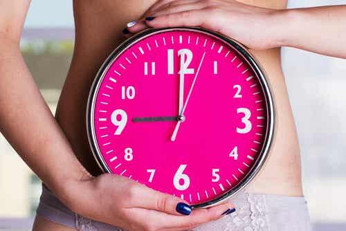 En kvinne som holder en klokke foran baren hennes.