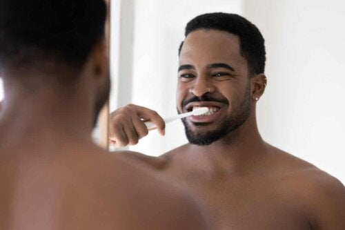 man in front of mirror smiling and brushing his teeth
