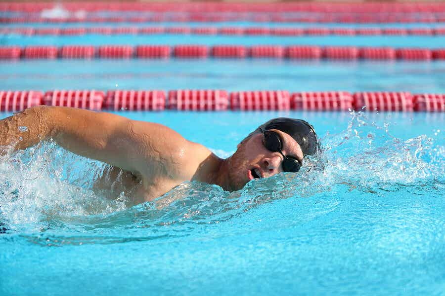 man swimming in pool with goggles and swim cap