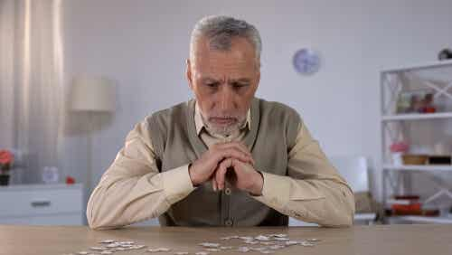 An elderly man focusing on the pieces of a puzzle.