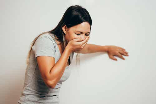 امرأة تغطي فمها بيدها لأنها تشعر بالغثيان.