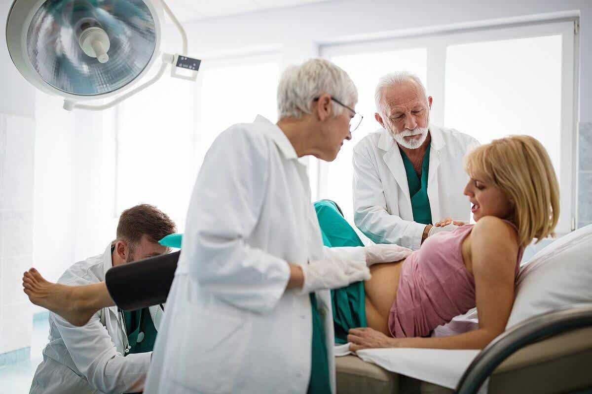 Μια έγκυος γυναίκα που παρακολουθείται από γιατρούς.