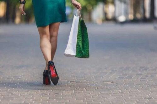 woman walking in heels carrying shopping bags