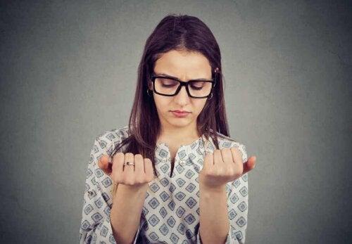 En kvinde undersøger sine negle