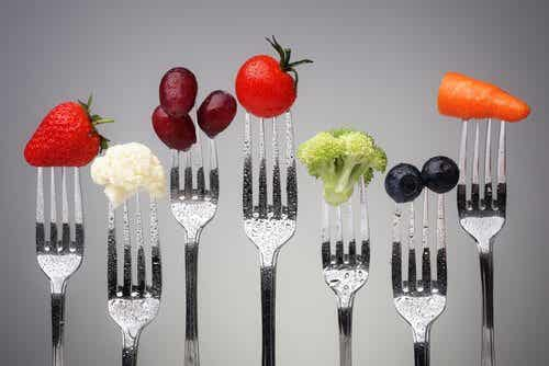 Several forks with fruit and vegetables.