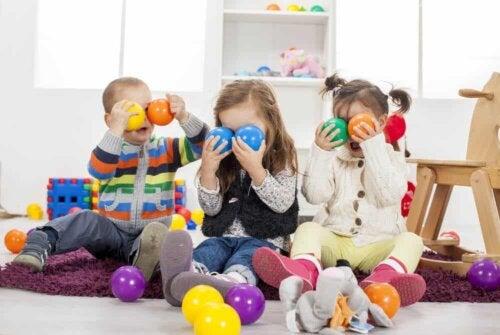 Tre børn leger med farverige bolde