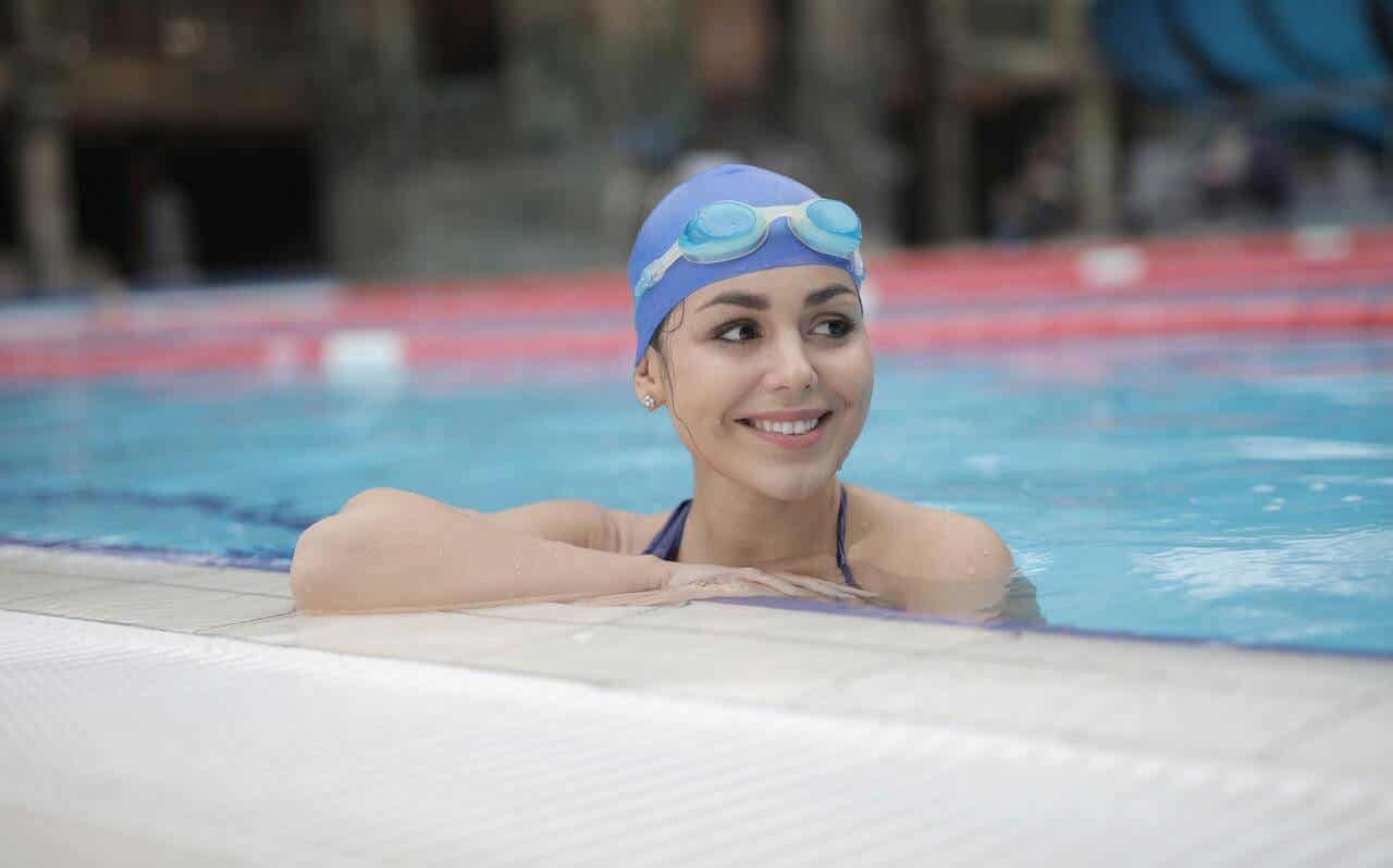 A girl smiling in a swimming pool.