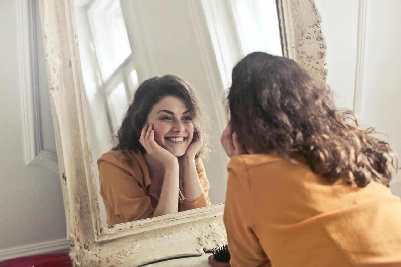 A woman smiling while looking in the mirror.