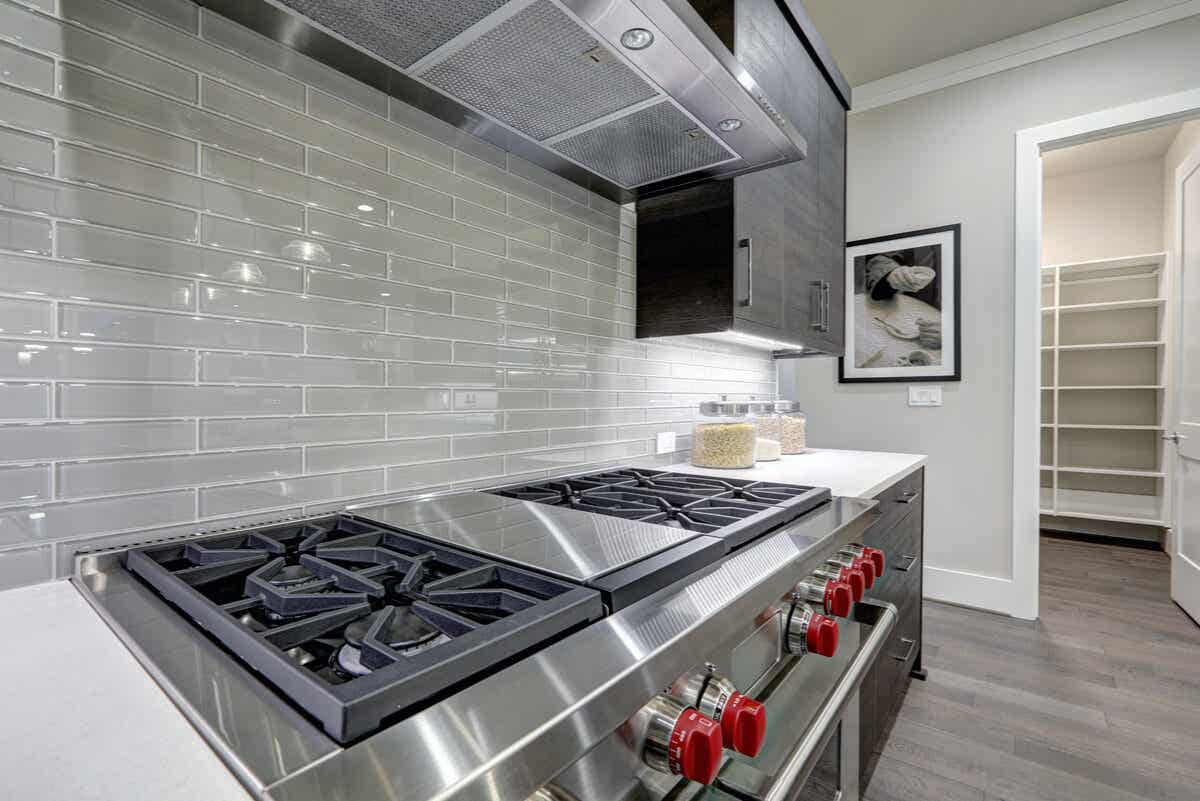 A kitchen with a metal stove and extractor.